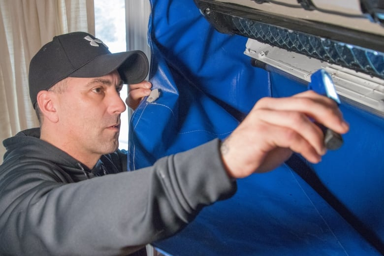 Billy Pashkoski looks inside his heat pump at his Middle Sackville home. (Robert Short/CBC)
